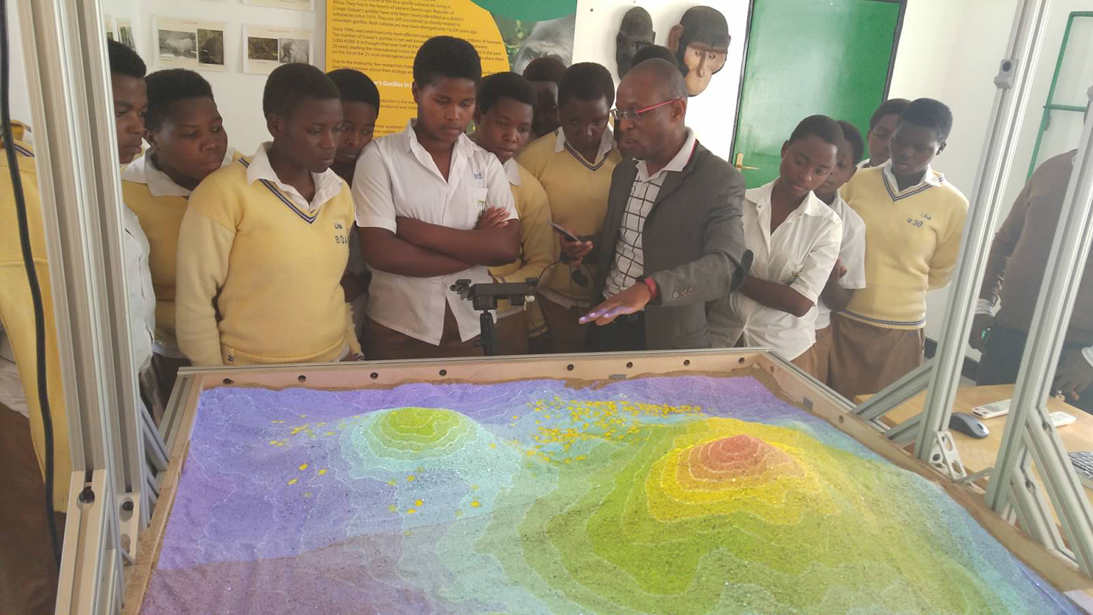 interactive sandbox with school children standing around it.